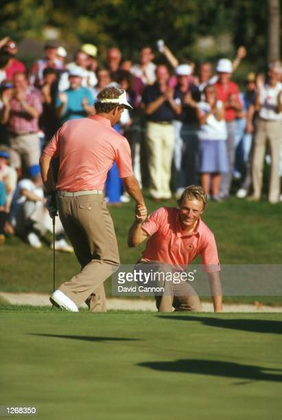 Sandy Lyle of Scotland helps Bernhard Langer of Germany out of a bunker during the Ryder Cup at Muirfield Village Golf Club in Ohio USA Europe won...