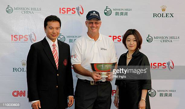 Sandy Lyle of Scotland is presented with the trophy by Tenniel Chu Executive Director Mission Hills China and Midori Miyazaki Executive Director...