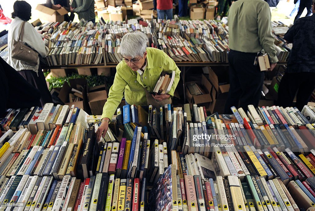 Sandy Morris goes through piles of books on tables set up under tents on the North Lawn outside the library. The Denver Public Library is holding it's 36th Annual Gigantic Used Book Sale. Over 70,000 items from children's books, nonfiction and fiction boo : Foto jornalística