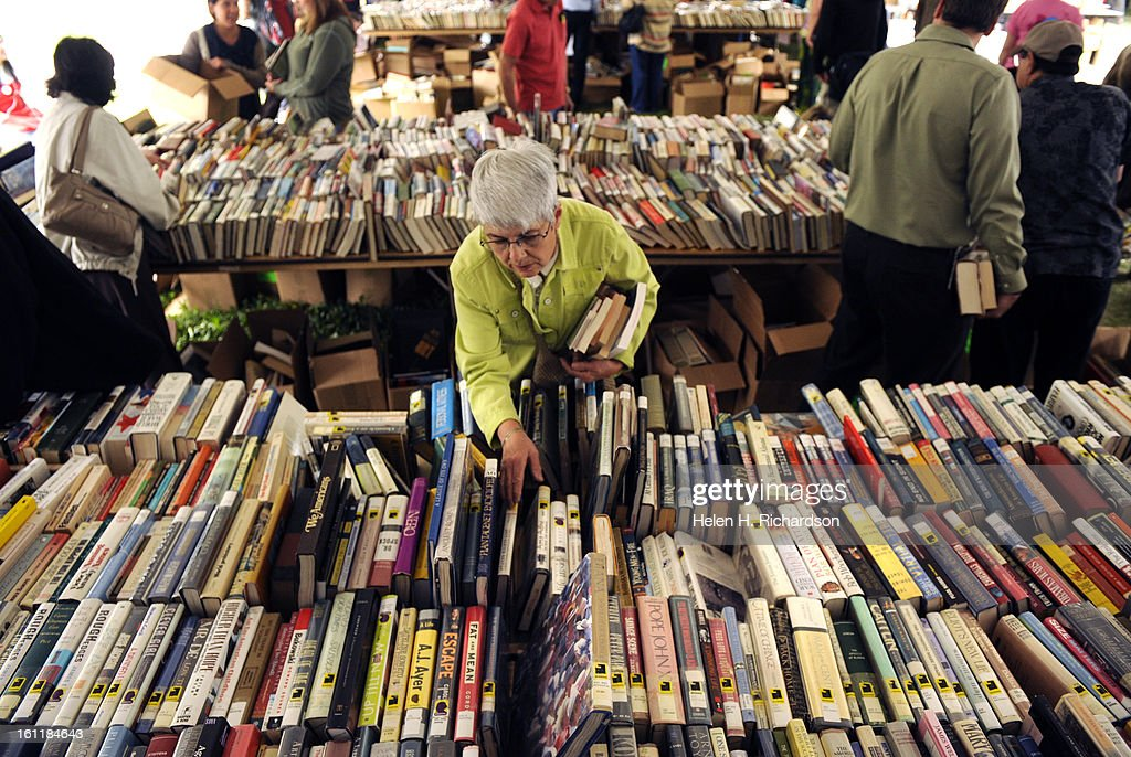 Sandy Morris goes through piles of books on tables set up under tents on the North Lawn outside the library. The Denver Public Library is holding its 36th Annual Gigantic Used Book Sale. Over 70,000 items from children's books, nonfiction and fiction book : News Photo