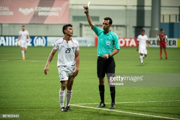 Sandy of Persija Jakarta is showed the yellow card by match referee Mooud Bonyadifard during the AFC Cup Zonal Semi final between Home United and...