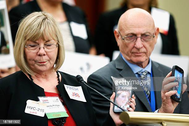 Sandy Phillips and her husband Lonnie Phillips hold up photos of their daughter Jessica who was killed in the Aurora Colorado movie theater shooting...