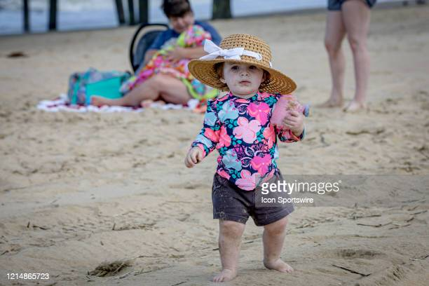A sandy toddler in a sun hat strolls across the beach on May 22 in Virginia Beach VA This is the first day of the beach's reopening for swimming...