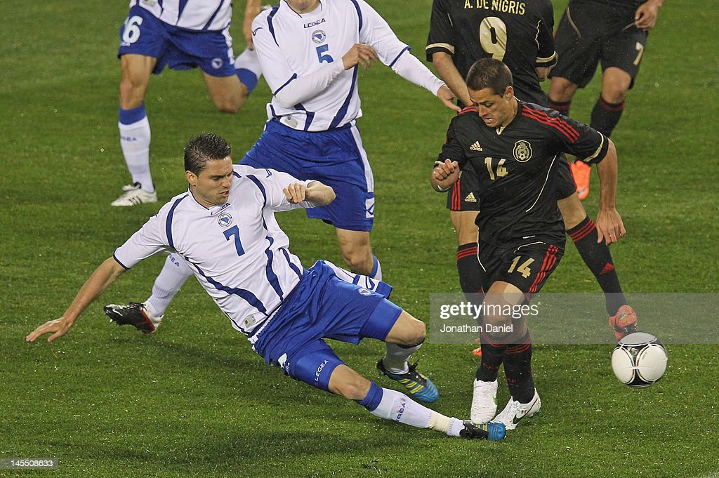Sanel Jahic #7 of Bosnia-Herzegovina kicks the ball away from Javier Hernandez #14 of Mexico during an international friendly at Soldier Field on May 31, 2012 in Chicago, Illinois. Mexico defeated Bosnia-Herzegovina 2-1.