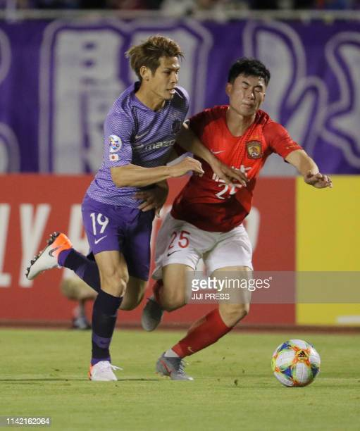 Sanfrecce Hiroshima defender Sho Sasaki and Guangzhou Evergrande defender Deng Hanwen fight for the ball during the AFC Champions League group F...