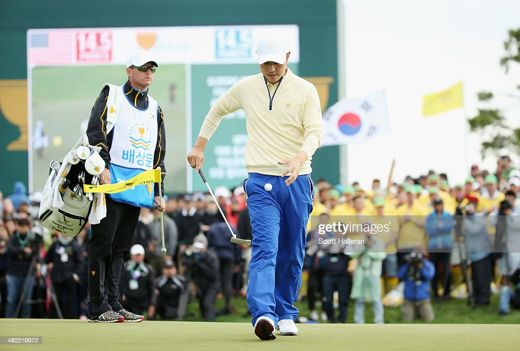 Sang-Moon Bae of the International Team picks up his ball on the 18h green in his match against Bill Haas of the United States Team as his caddie Matt Minister looks on during the Sunday singles matches at The Presidents Cup at Jack Nicklaus Golf Club Korea on October 11, 2015 in Songdo IBD, Incheon City, South Korea.