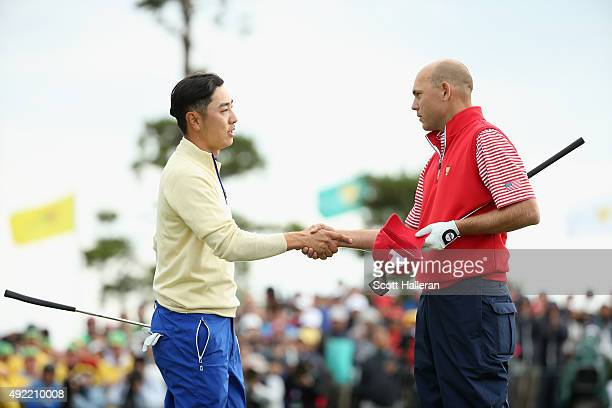 SangMoon Bae of the International Team shakes hands with Bill Haas of the United States Team on the 18h green after Haas won the match 2up during the...