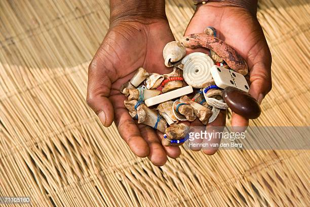 sangoma (traditional healer) hands holding bones - african witch doctor stock photos and pictures