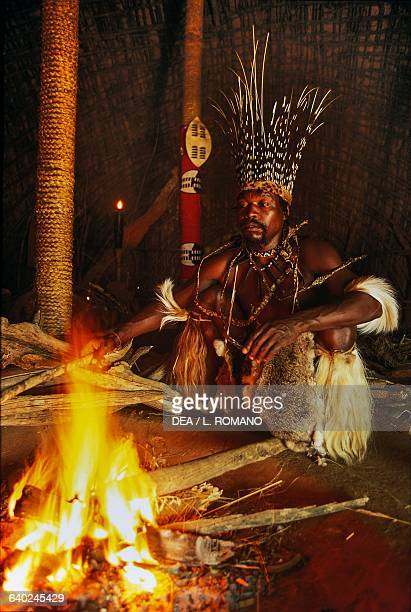 Sangoma in front of a fire Zulu village KwaZuluNatal South Africa
