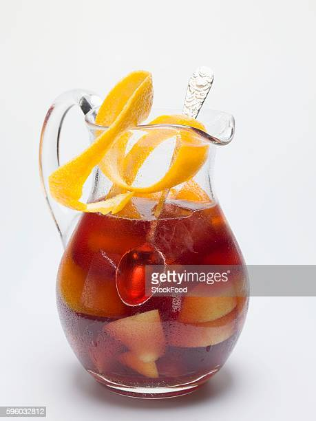 Sangria in a glass jug with orange peel