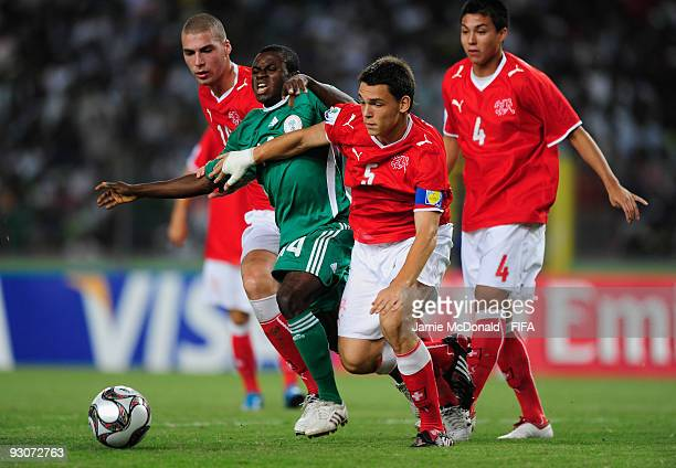 Sani Emmanuel of Nigeria battles with Pajtim Kasami and Frederic Vessel of Switzerland during the FIFA U17 World Cup Final match between Switzerland...