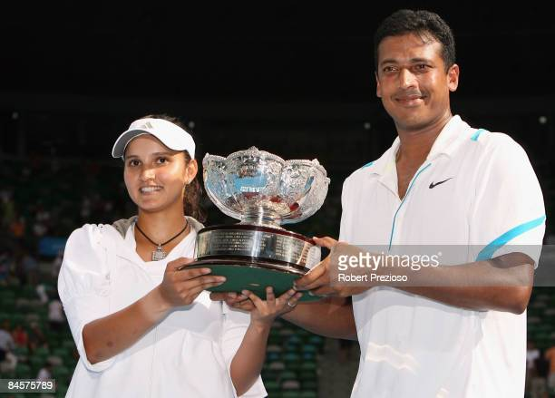 Sania Mirza and Mahesh Bhupathi of India pose with the championship trophy after winning their mixed doubles final match against Nathalie Dechy of...