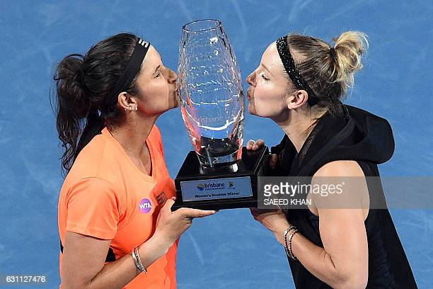 Sania Mirza of India and Bethanie Mattek-Sands of the US kiss their trophy after beating Russia's Ekaterina Makarova and Elena Vesnina in their...