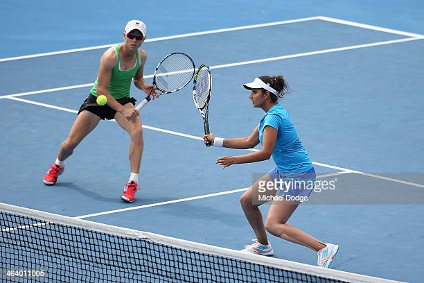 Sania Mirza of India and Cara Black of Zimbabwe in action in their third round doubles match against Eugenie Bouchard of Canada and Vera Dushevina of...