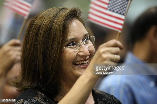 Sania Stiles who came to the US from Monterrey Mexico eight years ago waves a flag upon gaining US citizenship as 18418 people are sworn in as US...