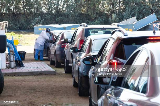 Sanitary woman worker stands between two rows of cars of elderly people waiting to be vaccinated with the Pfizer vaccine outside the Polideportivo...