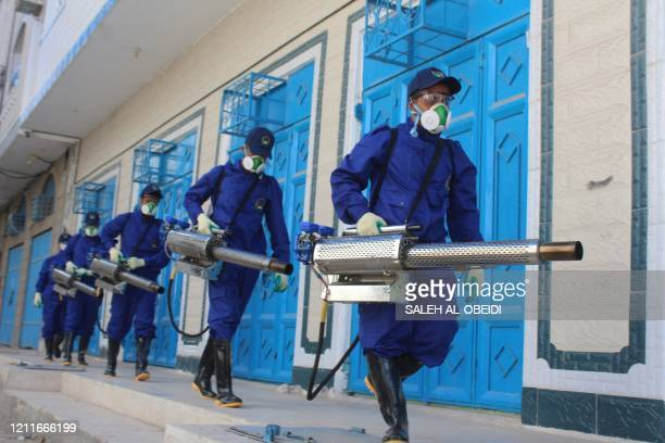 Sanitary workers prepare to perform a fumigation in an area in Yemen's southern coastal city of Aden on May 3 as part of a campaign to prevent...