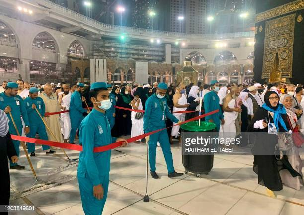 Sanitary workers wearing protective face masks continue to clean the sahn surrounding the Kaaba Islam's holiest shrine as Muslim worshippers pray at...