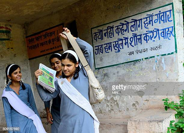 Sanitation quotes written on wall to promote Swachh Bharat Abhiyan as school girls pass by on February 23 2015 in New Delhi India