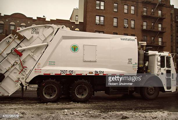 Sanitation truck passes through a snowy Midwood street in Brooklyn,NY.