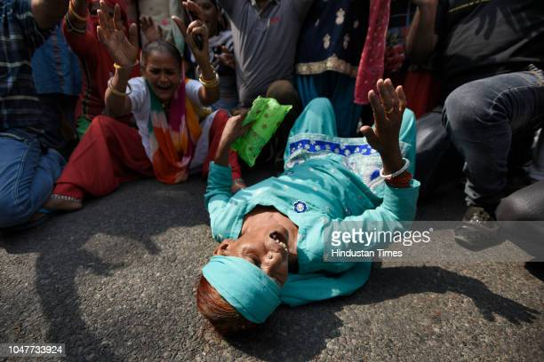 A sanitation worker of the Municipal Corporation of Delhi lies on the ground as she shouts slogans after police baton charged them when they tried to...