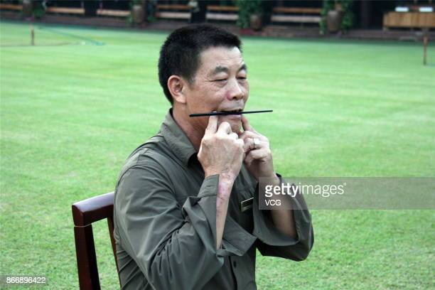 A sanitation worker practices smiling by biting on chopsticks at Chuanlord Tourism and Leisure Expo Park on October 26 2017 in Foshan Guangdong...