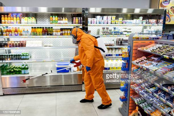 Sanitation worker sprays disinfectant inside a convenience store in the Cypriot capital Nicosia on March 20, 2020. - The Republic of Cyprus has...