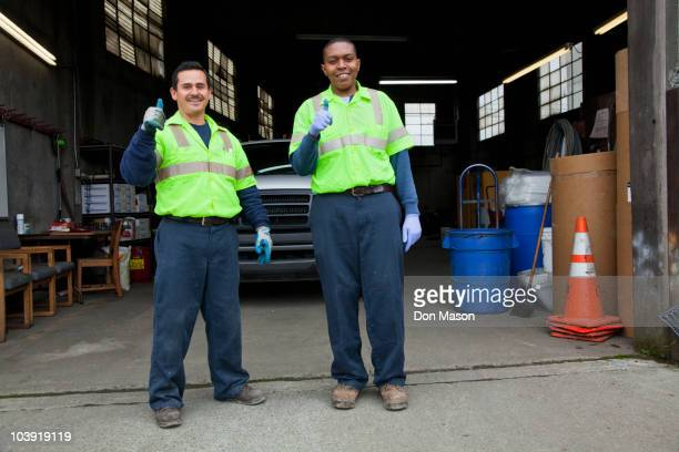 sanitation workers giving thumbs up in garage - eboueur photos et images de collection