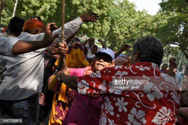 Sanitation workers of the Municipal Corporation of Delhi scuffle with the police after police baton charged them when they tried to cross the police...