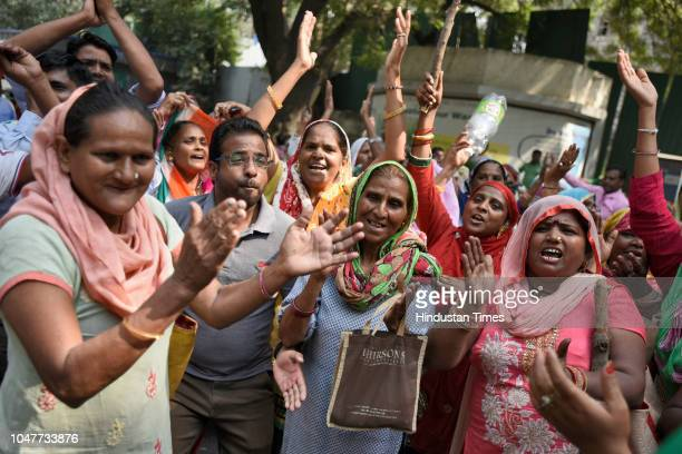 Sanitation workers of the Municipal Corporation of Delhi shout slogans after police baton charged them when they tried to cross the police...