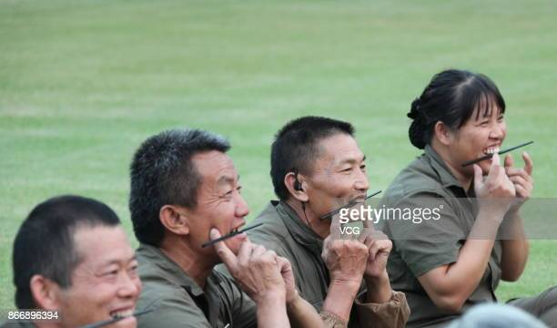 Sanitation workers practice smiling by biting on chopsticks at Chuanlord Tourism and Leisure Expo Park on October 26 2017 in Foshan Guangdong...