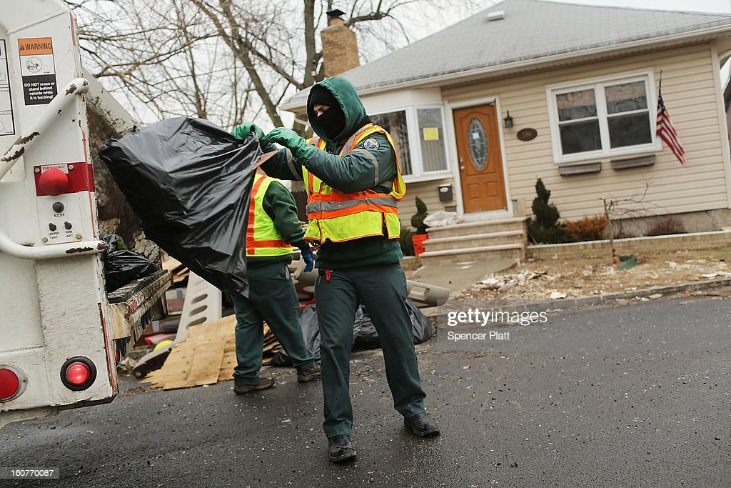 Sanitation workers thrrow out debris from a flood damaged home in Oakwood Beach in Staten Island on February 5, 2013 in New York City. In a program proposed by New York Governor Andrew Cuomo, New York state could spend up to $400 million to buy out home owners whose properties were destroyed by Superstorm Sandy. The $50.5 billion disaster relief package, which was passed by Congress last month, would be used to fund the program. If the program is adopted, homeowners would be relocated and their land would be left as a natural barrier to help absorb future floods waters.