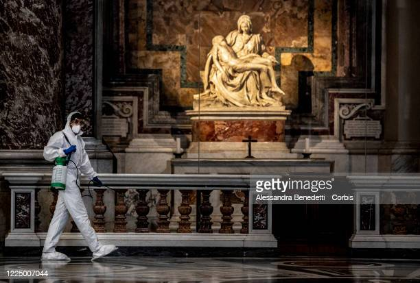 Sanitation workers use special equipment to clean and disinfect St. Peter's Basilica in front of Michelangelo's Pieta, as a preventive measure...