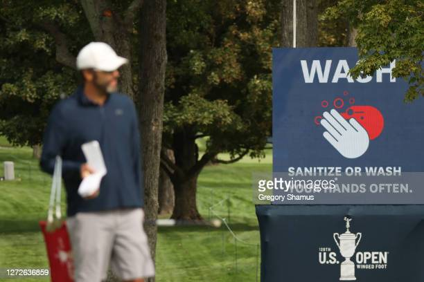 """Sanitize or Wash Your Hands Often"""" sign is seen as a caddie waits on a green during a practice round prior to the 120th U.S. Open Championship on..."""