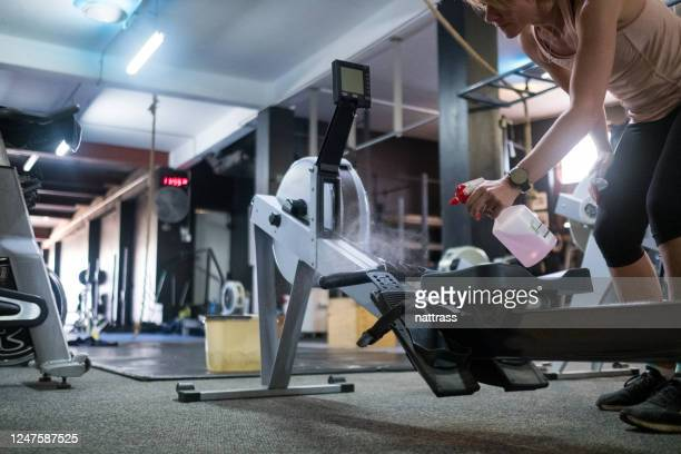 sanitizing exercise equipment in the gym - opening event stock pictures, royalty-free photos & images