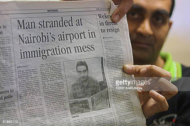 Sanjai Shah holds up a newspaper highlighting his plight during an interview with AFP 13 December 2004 at the Jomo kenyatta International Airport...