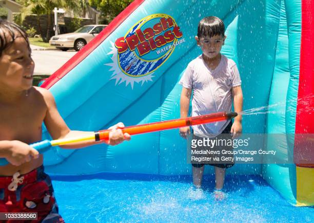 Santa Ana residents Aiden Ryan Guzman left shoots a water hose as his neighbor Nathan Perez cools off in a water shower as the temperature in Orange...
