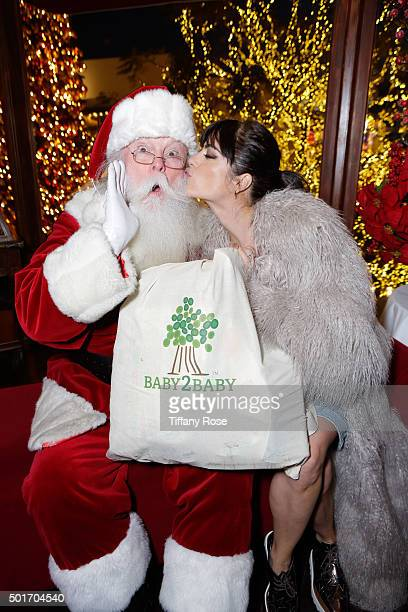 Santa and actress Selma Blair pose at the Baby2Baby holiday event at The Grove on December 16 2015 in Los Angeles California