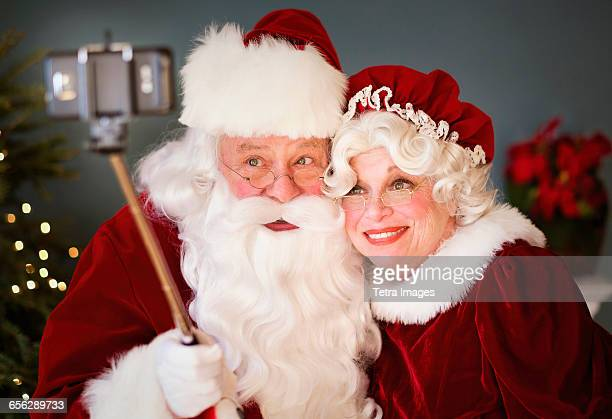 santa and mrs. santa taking selfie with monopod - santa close up stock pictures, royalty-free photos & images