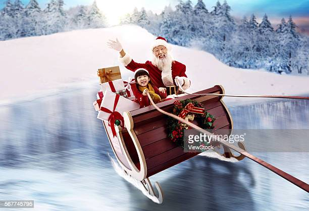 Santa and the little girl sat on the sled to send a gift
