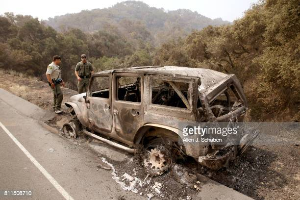 Santa Barbara deputy Sheriff B Bruening left and US Fish Wildlife game warden Max Magleby view a jeep that was abandoned and scorched by the Whittier...