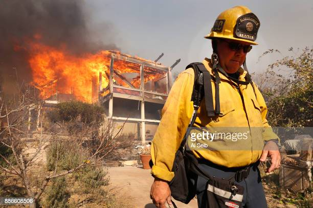 Santa Barbara PIO Mike Eliason watches as a home between Via Baja and Foothill goes up in flames Tuesday midday after a fastmoving windfueled...