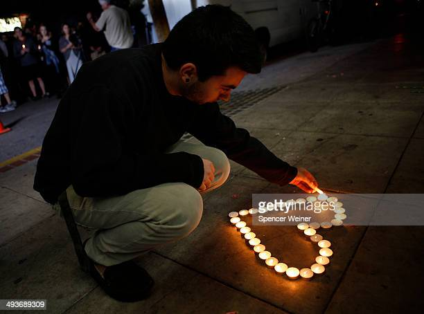 Santa Barbara student Eldar Erlich lights candles at a growing memorial in front of the IV Deli Mart on Pardall Road in Isla Vista on May 24 2014 in...