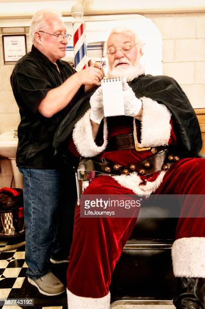santa checking his naughty or nice list while getting a last minute haircut at the barber's - naughty santa stock photos and pictures