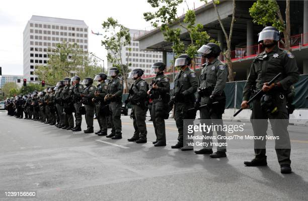 Santa Clara County Police officers line up next to San Jose Police officers during a protest of the killing of George Floyd outside of San Jose City...