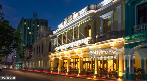 santa clara, cuba: hotel central (illuminated yellow building), long exposure at night - santa clara cuba stock pictures, royalty-free photos & images