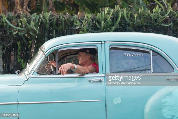 Santa Clara, Cuba: senior man driving an old Chevrolet car in the Central Road