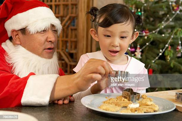 santa claus and a girl making christmas cookies. - zakelijke kleding stock pictures, royalty-free photos & images
