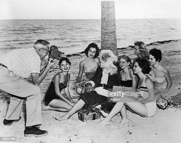 Santa Claus and a group of sunbathers posing for a cameraman on a beach in Miami Florida