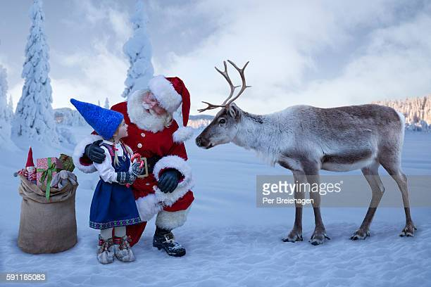 Santa Claus and a reindeer with a young girl